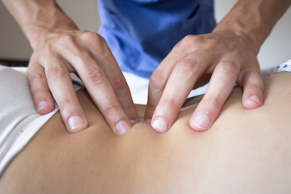 osteopath hands on patient back